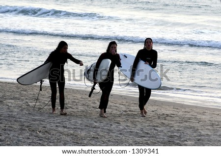 girl surfurs walk on the beach with their boards after a long surfing day.