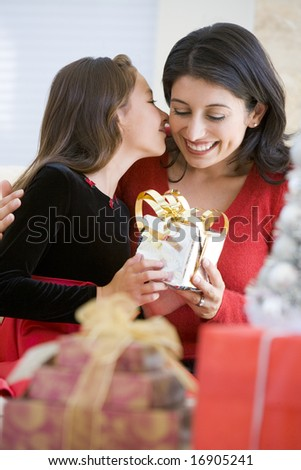 Girl Surprising Her Mother With Christmas Gift - stock photo