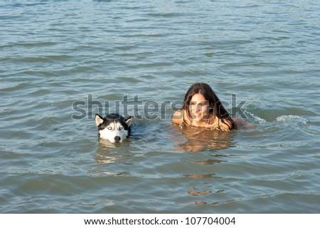 girl swim with Husky dog - stock photo
