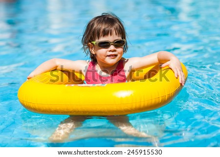 Girl swimming in a pool. Cute little girl swims in a pool in a yellow life preserver - wearing sunglasses - stock photo
