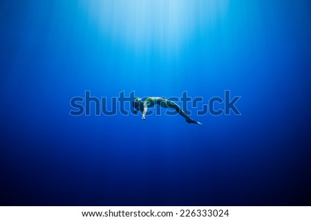 girl swimming underwater in a deep blue tropical sea