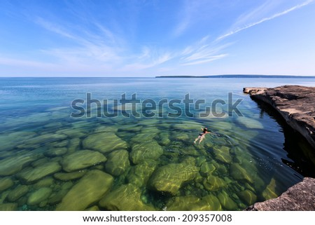 Girl swims in Lake Superior in the Upper Peninsula of Michigan. Rocks are visible through the glass like, pristine waters. Pictured Rocks National Lakeshore is in the distance. - stock photo