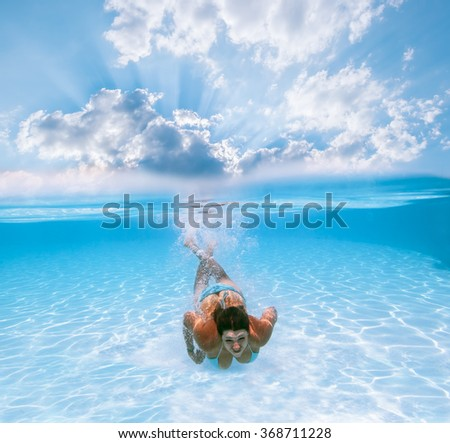 Girl swims under water in the pool against the backdrop of the beautiful heavenly scenery