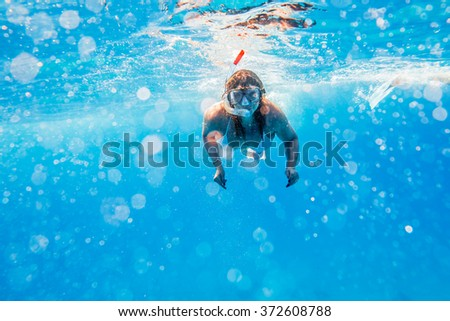 Girl swims under water with mask in blue sea - stock photo