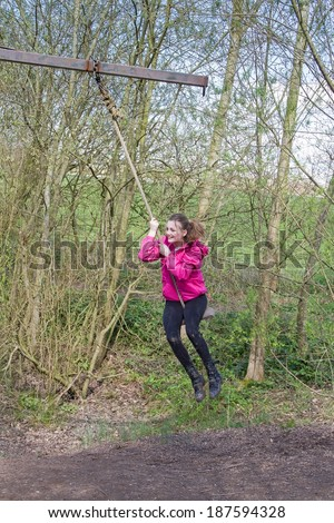 Girl swinging around on a rope swing