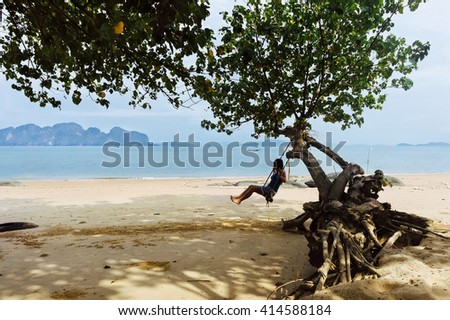 Girl swinging at a tropical summer beach in Thailand. Tropical beach paradise with rope swings on a tree. Summer tropical resort near beautiful sea beach. Tropical beach swings. Tropical landscape - stock photo