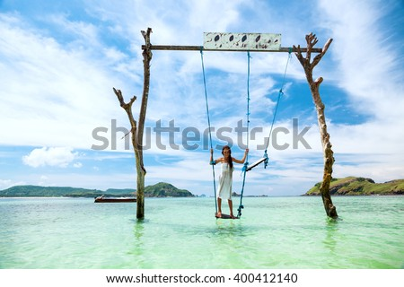 Girl swinging at tropical beach, sunny day, good weather. Swinging in paradise island. - stock photo