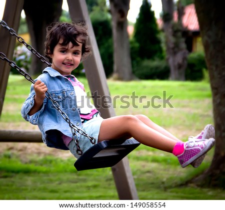 girl swinging in a park - stock photo