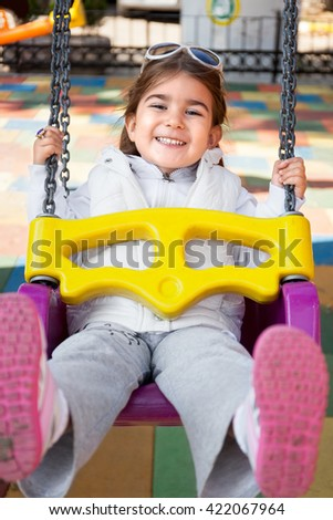 Girl swinging in park - stock photo