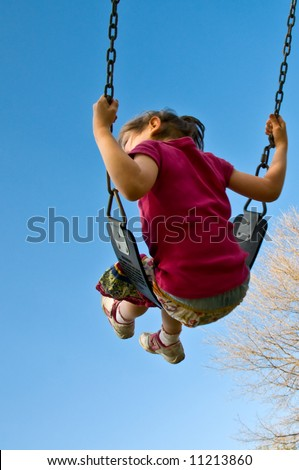 girl swings high into a blue sky vertical