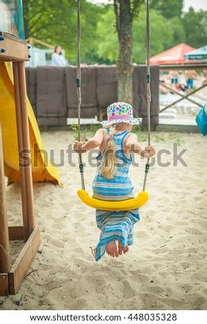 girl swings. Little child blond girl having fun on a swing outdoor. Summer playground. Kids play on school yard. Happy kid in kindergarten or preschool. Children having fun at daycare play ground. - stock photo
