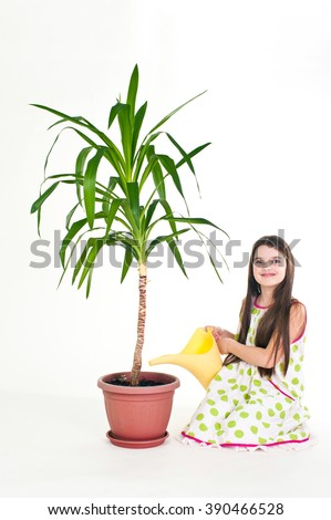 Girl takes care of yucca plant on white