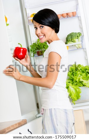 Girl takes red pepper from the opened fridge full of vegetables and fruit. Concept of healthy and dieting food
