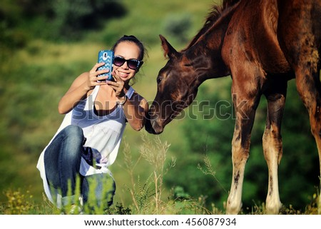Girl takes selfie with foal - stock photo