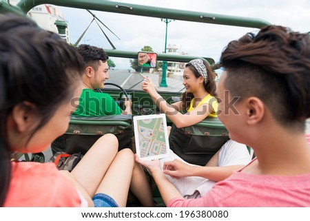 Girl taking a picture of the car driver while her friends on the backseat are using tablet with navigator on the screen - stock photo