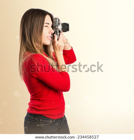 Girl taking a picture over ocher background