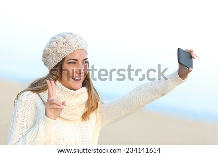 Girl taking a selfie with her smart phone warmly clothed in winter on the beach - stock photo