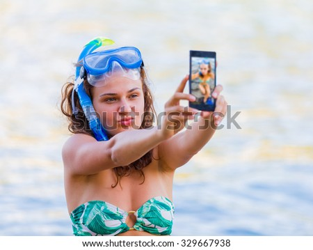 Girl taking a selfie with her smartphone at the sea making duckface at the sea before uploading the photo to Facebook. - stock photo
