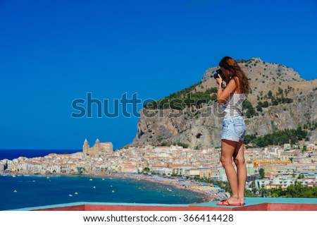 Girl taking photo from a bird-view point with Cefalu town and the sea on the background, Sicily, Italy. - stock photo