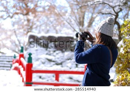 Girl Taking photo in snow scene - stock photo