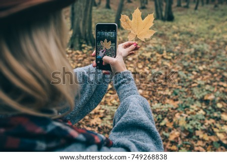 Girl taking picture outdoor. Upload it to social media.