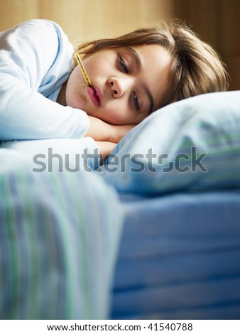 girl taking temperature in bed. Copy space