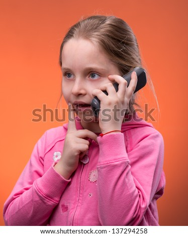 Girl talking on a cell phone on an orange background - stock photo