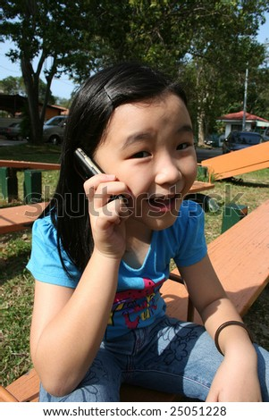 Girl talking on mobile phone in the park