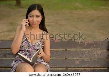 Girl talking on mobile phone outdoors in park