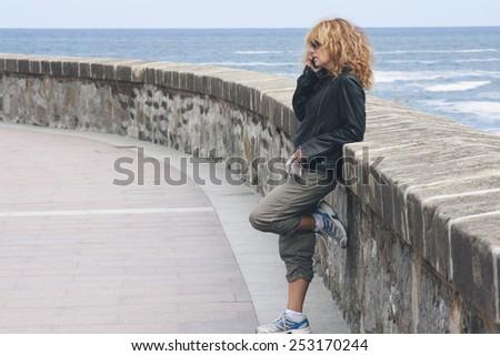 girl talking on phone on the beach - stock photo