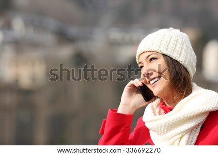 Girl talking on the mobile phone warmly clothed in winter - stock photo
