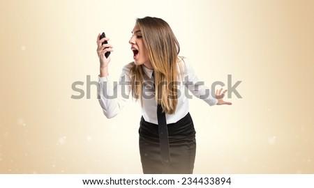 Girl talking to mobile over ocher background.  - stock photo