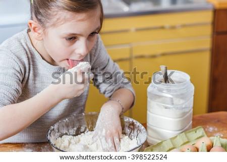Girl tasting fresh flour - stock photo
