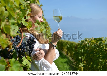 Girl tasting white wine among vineyards. Lavaux, Switzerland