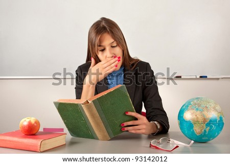 Girl teacher reading book and yawn