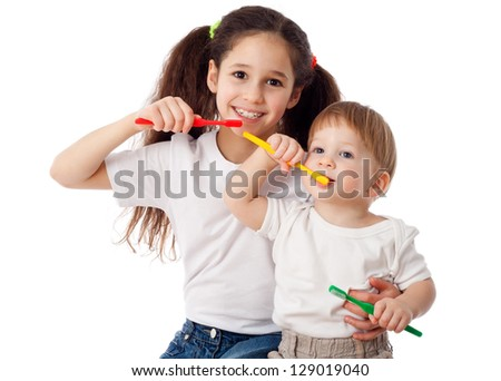 Girl teaches little boy brushing teeth, isolated on white - stock photo