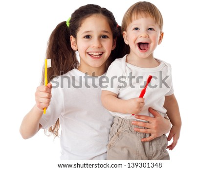 Girl teaches little boy brushing the teeth, isolated on white - stock photo