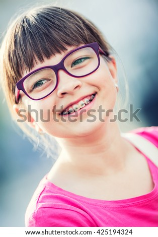 Girl. Teen. Pre teen. Girl with glasses. Girl with teeth braces. Young cute caucasian blond girl wearing teeth braces and glasses. - stock photo