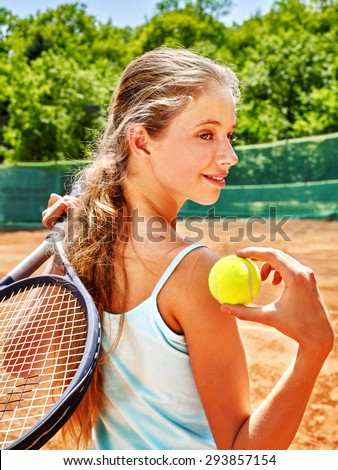 Girl teen sportsman in blue shirt swith racket and ball  on  tennis court.  - stock photo
