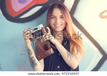 Girl teen with vintage camera against the wall of graffiti looks away. Solar flare in the frame.