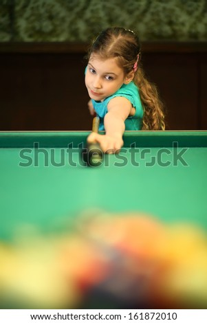 Girl teenager begins the game of billiards in the billiard hall