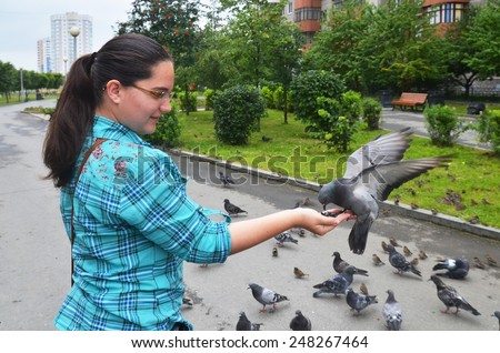 girl teenager holding pigeon on the hand and feeding him