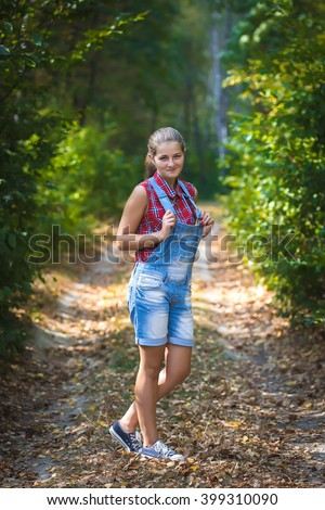 Girl teenager in denim jumpsuit standing, on the road in summer forest. portrait with natural light on outdoors.