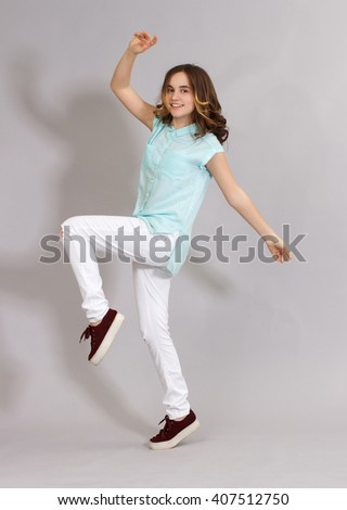 Girl teenager in fashionable clothes have fun jumping on a black background .