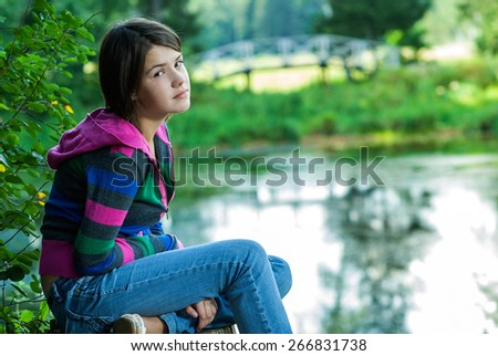 Girl-teenager in striped jacket with hood sits on big stub which is on bank of lake. - stock photo
