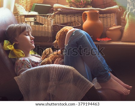 Girl teenager in the attic or in the pantry sits in an old chair with a toy. Lots of sun, the sun's rays. The girl speaks with a toy. Many different items