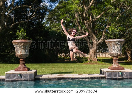 Girl Teenager running jumping into swimming pool summer playtime - stock photo