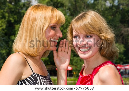 Girl telling a secret to another gossip. Two happy women sharing funny gossip. Gossip - two beautiful girls.  Happy young women friends talking and laughing.  Woman i is telling a secret to another. - stock photo