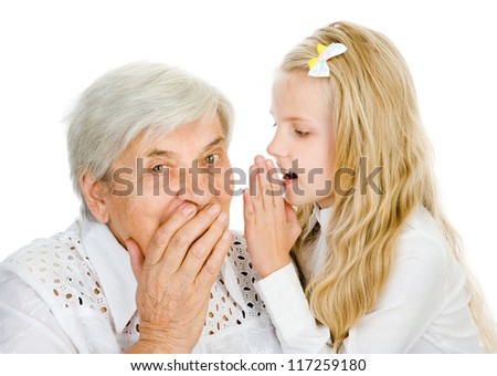 girl telling an astonished old woman some secrets. isolated on white background