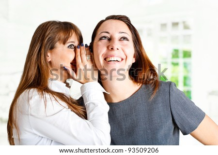 Girl telling funny news to her friend - stock photo